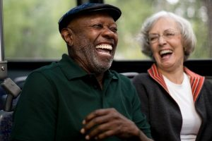 an older couple laugh together - black man, white woman - on the bus
